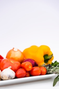 Close-up of healthy fresh organic vegetables in tray over white background