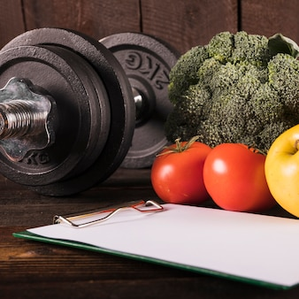 Close-up of healthy raw food and dumbbell on wooden desk