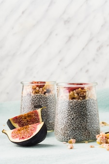 Close-up of healthy smoothie and fig fruit slices over place mat