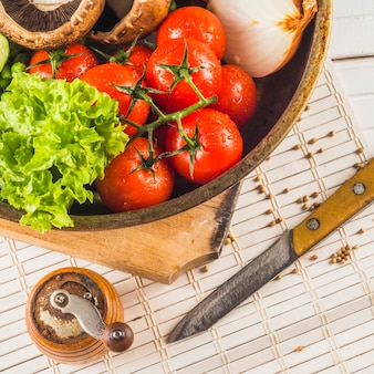 Close-up of healthy vegetable; knife; spice grinder on placemat