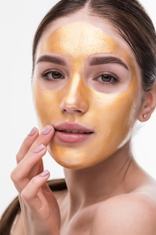 Close up of healthy young woman with gold cosmetic face mask on soft skin.