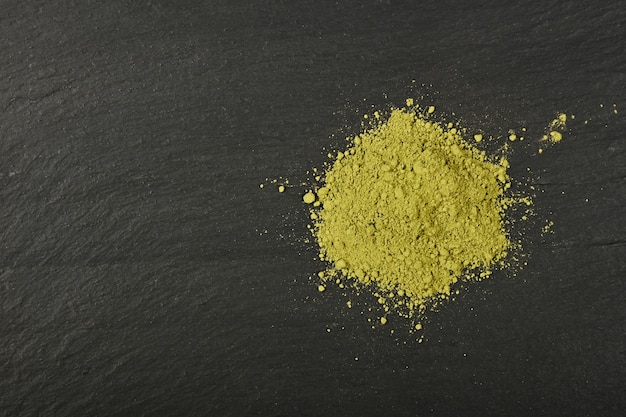 Close up heap full of ground unroasted raw green arabica coffee on black slate board background, elevated top view, directly above