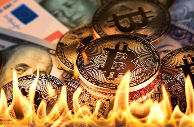 Close up heap of golden bitcoin physical coins and paper money banknotes burning in fire flames, as symbol of economy crisis, decline and market crash or disruption