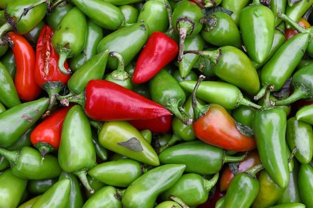 Close up heap of many fresh green and red hot jalapeno chili peppers on retail display at farmers market, elevated top view, directly above