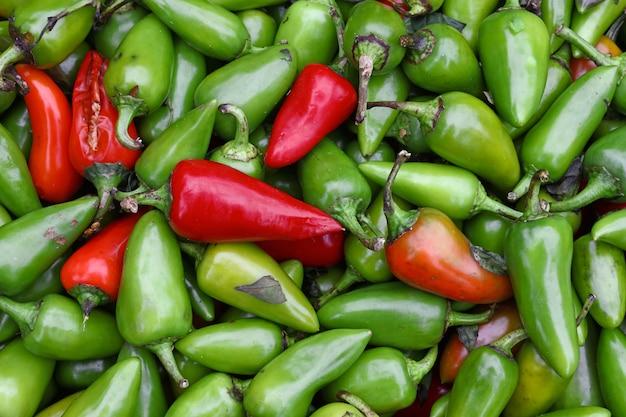 Крупным планом кучу свежих зеленых и красных острых перцев чили халапеньо на розничной витрине на фермерском рынке, вид сверху, прямо над