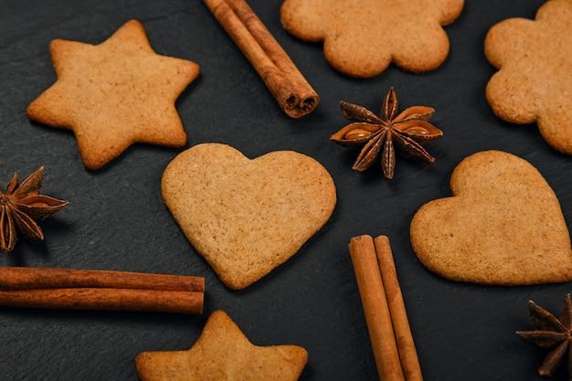 黒のスレートの背景、高架の上面図、真上にシナモンとスターアニスのスパイスでハートと星型のクリスマスジンジャーブレッドクッキーを閉じます