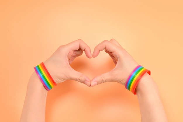 Close up of heart made by woman hands with pale skin isolated on white background. lgbt.