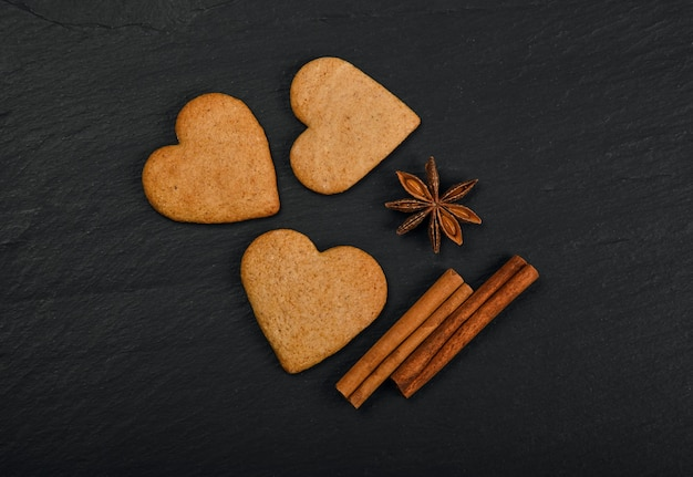Close up heart shaped gingerbread cookies with cinnamon and star anise spices on black slate background with copy space, elevated top view, directly above