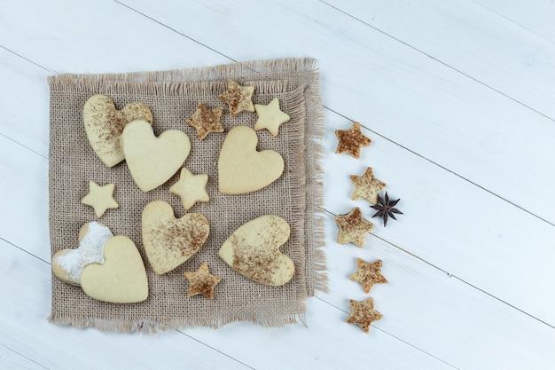 Biscotti a forma di cuore e stella del primo piano sul pezzo di sacco con i biscotti della stella sul fondo del bordo di legno bianco. orizzontale