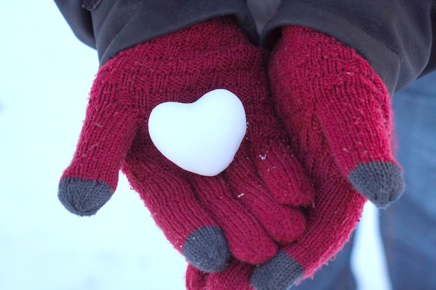 Close-up to a heart snowball in womans hands