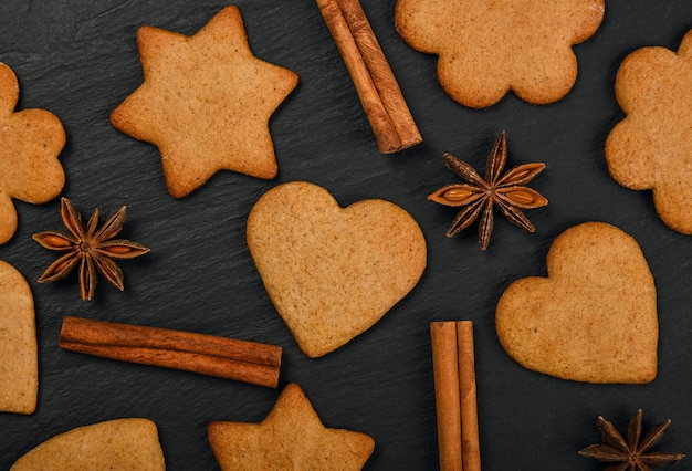 Close up heart and star shaped christmas gingerbread cookies with cinnamon and star anise spices on black slate background, elevated top view, directly above
