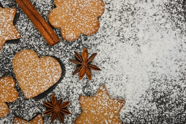 Close up heart and star shaped christmas gingerbread cookies with cinnamon and star anise spices on black slate background with powdered white sugar icing, elevated top view, directly above