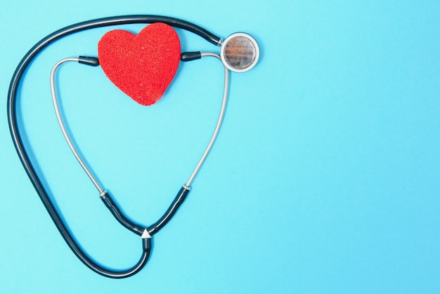 Close-up of a heart and a stethoscope on a blue background, top view. global health care concept. caring for heart health. treatment with tablets and ampoules