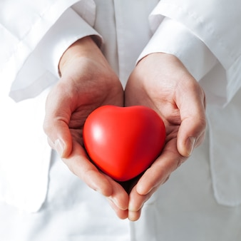 Close-up. heart symbol is in the doctor's hands. concept of health protection.