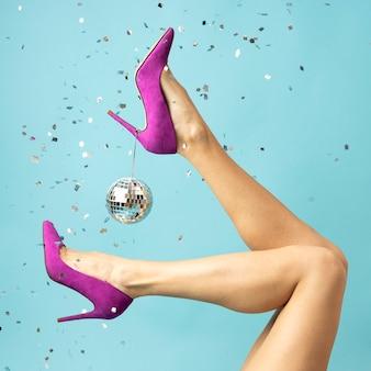 Close up heels, confetti and disco globe