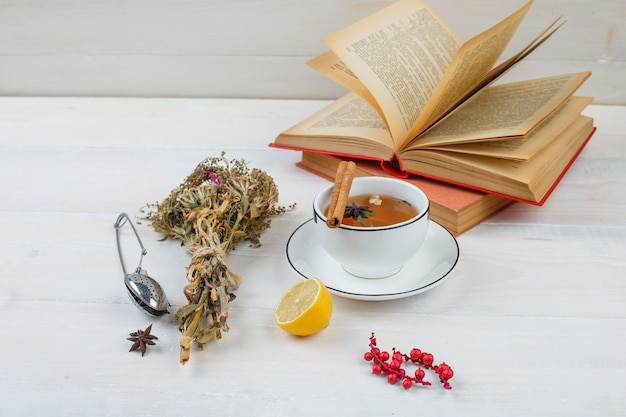 Close-up of herbal tea and flowers with lemon, tea strainer and spices