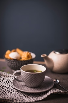 Close-up of herbal tea with bowl of cookies and teapot in background