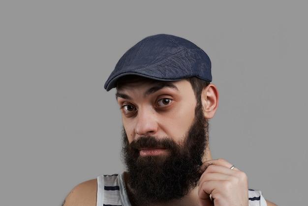 Close up alto ritratto dettagliato di uomo barbuto caucasico isolato su sfondo grigio e guarda alla telecamera.