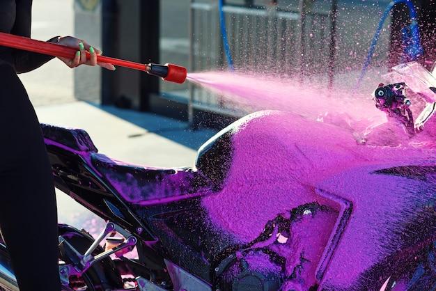 Крупным планом розовая пена высокого давления моет мотоцикл на автомойке самообслуживания. выборочный фокус.
