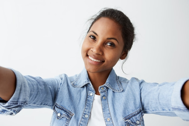 Close up highly-detailed portrait of attractive good-looking afro-american woman with black hair and dark skin, casually dressed  with pleasant expression and charming smile.