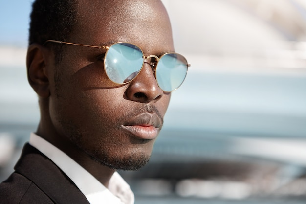 Close up highly-detailed shot of handsome serious afro american office worker in formal wear and mirrored lens shades posing in urban surroundings, thinking about prospects and possibilities at work