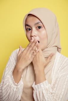 Крупным планом женщины в хиджабе с шокированным выражением лица перед камерой, изолированной на желтом фоне