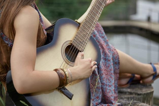 확대. 숲 호수 근처에서 기타를 연주하는 히피 여자