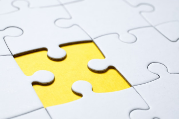 Close up of hole in white jigsaw puzzle on yellow .