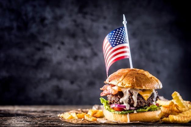 근접 집에서 만든 쇠고기 버거와 미국 국기와 감자 튀김이 나무 테이블에 있습니다.