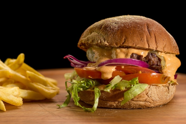 Close up of a homemade burger with salad on a chopping wood board