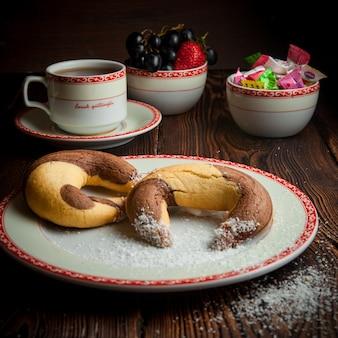 一杯のお茶と木製のテーブルのお菓子とクローズアップの自家製クッキー