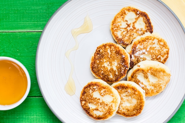 Close-up of homemade cottage cheese pancakes with honey on a plate on a wooden table. top view