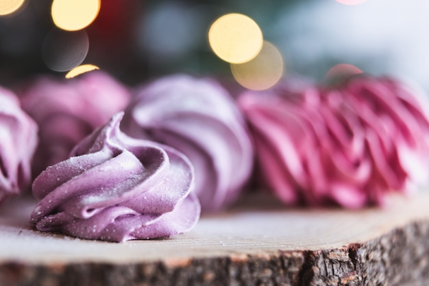 Close up of homemade cut pink zephyr or marshmallow in powdered sugar on wooden with abstract bokeh . black currant, blueberry marshmallows.