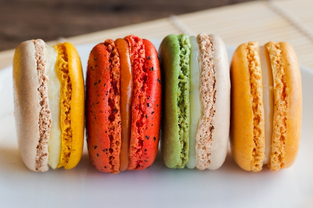 Close up homemade delicious colorful french or italian macarons stack on white plate.
