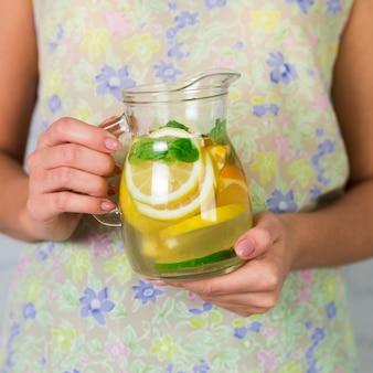 Close up homemade lemonade jug held by woman