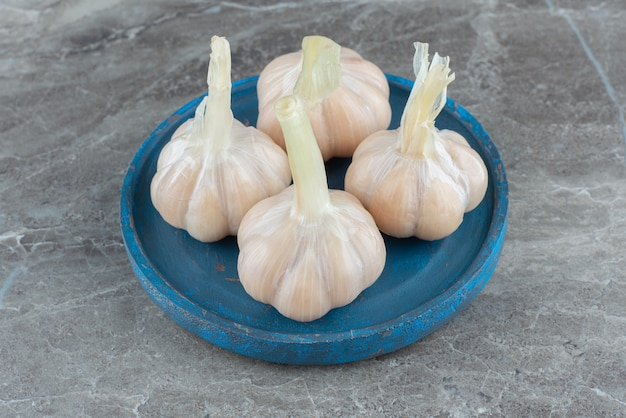 Close up of homemade pickled garlic on blue wooden plate