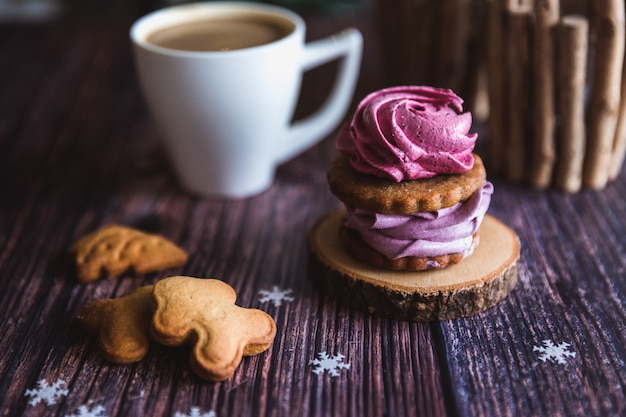 Close up of homemade pink and purple zephyr or marshmallow in powdered sugar with white mug on wooden. black currant, blueberry marshmallows.