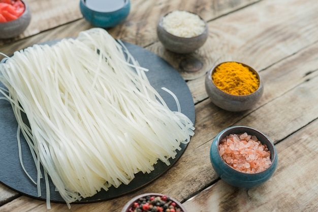 Close-up of homemade rice vermicelli and fresh ingredients over wooden bench