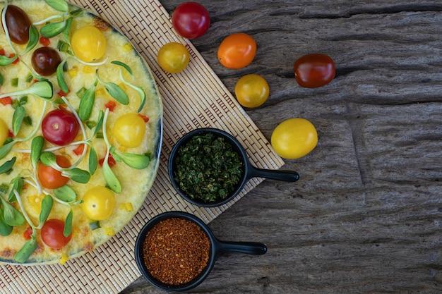 木製の背景にチェリートマトと他の材料で自家製野菜ピザをクローズアップ