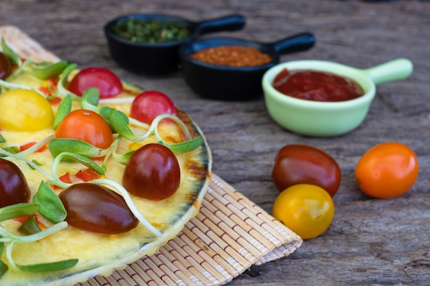 나무 배경에 체리 토마토와 다른 재료로 만든 야채 피자를 닫습니다