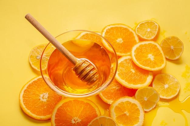 Close-up honey bowl with orange slices