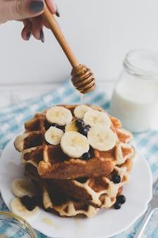 Close-up honey pouring onto waffles