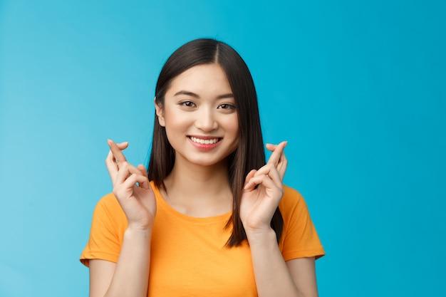 짧은 검은 머리를 가진 귀여운 아시아 소녀가 행운을 빕니다, 긍정적인 소식을 기다리며 활짝 웃고, 성실하게 승리를 희망하고, 파란색 배경에 서서 흥분을 하고 있습니다.