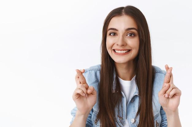 Primo piano speranzoso, ottimista ragazza bruna carina crede che i sogni diventino realtà, aspira e sogna, incrocia le dita per buona fortuna, sorride, prega e anticipa buone notizie, sfondo bianco