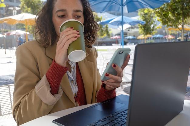 클로즈업 수평으로 클로즈업된 라티나 여성은 휴대전화를 보고 노트북으로 작업하면서 커피를 마시고, 디지털 유목민 개념, 복사 공간
