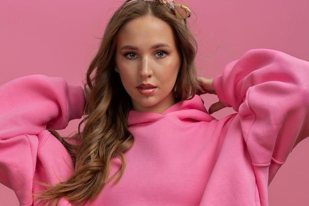 ピンクの背景にピンクの特大のパーカーで若い女性の水平方向の肖像画を閉じる