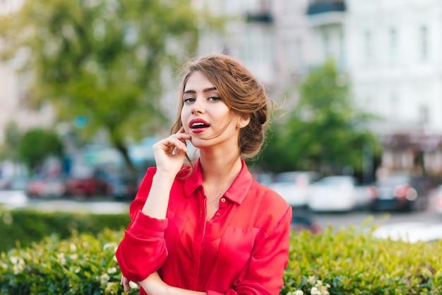 公園に立っている素敵なヘアスタイルでかわいい女の子の水平のクローズアップの肖像画。彼女は赤いブラウスを着ています。彼女はカメラを見ています。