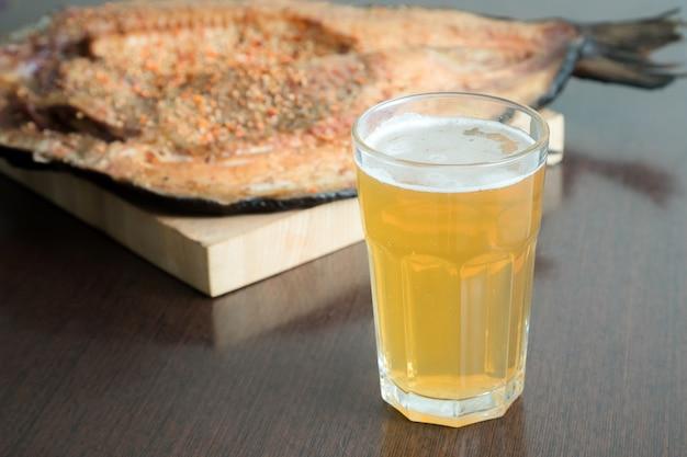 木製のサービングボードと冷たいビールのガラスの調味料で魚の燻製フィレの水平方向のビューを閉じます。