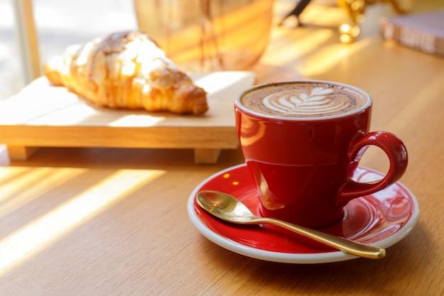 Закройте вверх по горячему капучино, латте, карамель макиато на столе с размытым кафе.