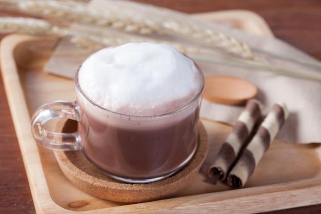 Закрыть горячее шоколадное молоко с закуской на деревянной тарелке на деревянный стол на завтрак.
